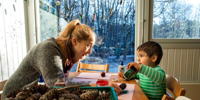 Barnehagelærer gjør kunst og håndverk med et barn i barnehagen.