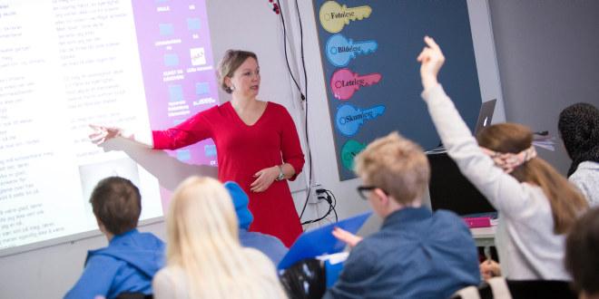 Lærer på ungdomsskolen underviser en klasse. En elev har hånden i været.