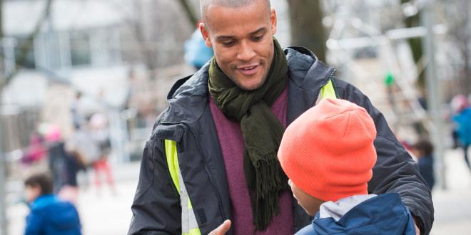 Lærer snakker med gutt i skolegården.