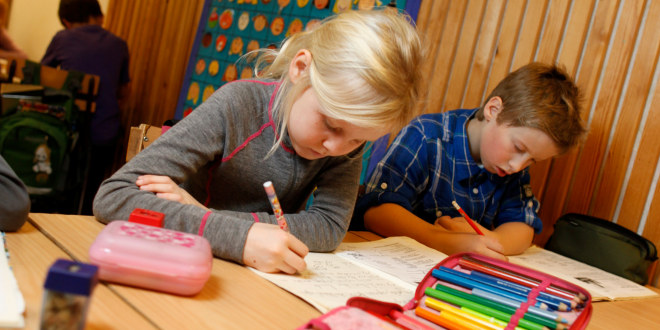 To barn skriver på en prøve i klasserommet.