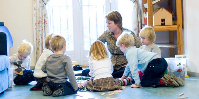 Barnehagelærer leker sammen med barn på gulvet.