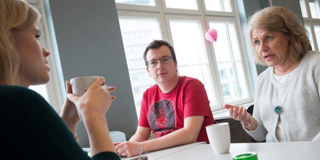 Tre lærere diskuterer rundt et bord