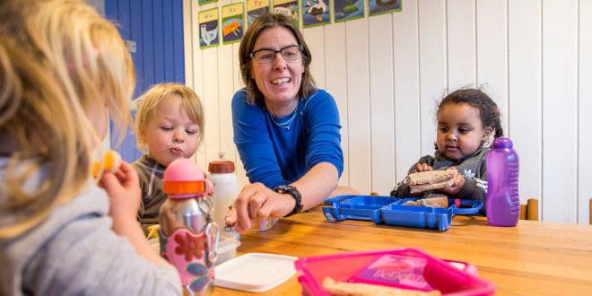 barnehagelærer med barnehagebarn som spiser mat