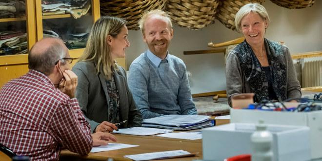 Fire lærere sitter rundt et bord og prater muntert