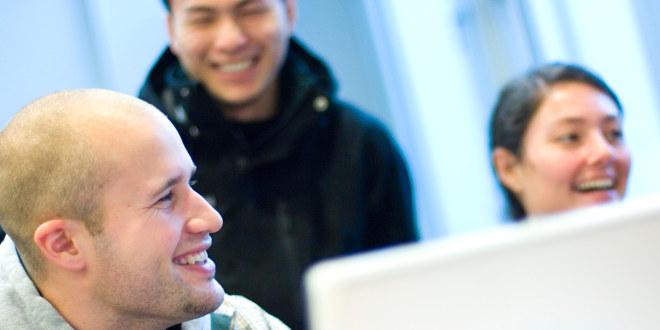 Lærerstudenter smiler og ler mens de jobber sammen rundt en datamaskin.