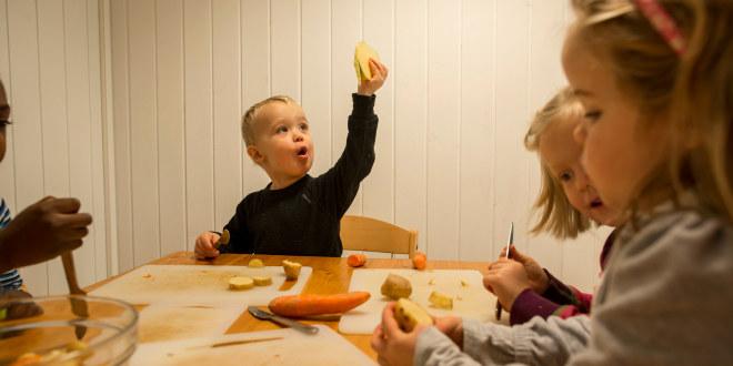 Barn skjærer poteter og gulerøtter i barnehagen.