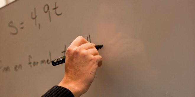 En hånd som skriver på en tavle