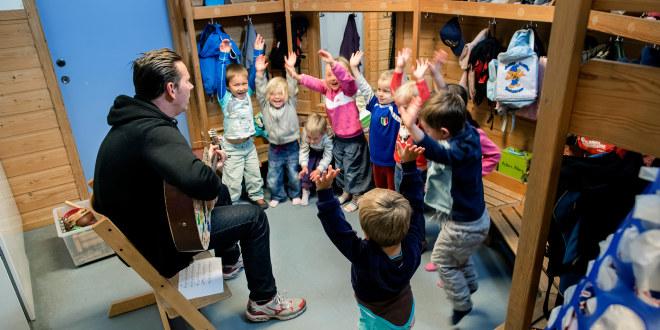 Barnehageansatt spiller gitar og barna danser