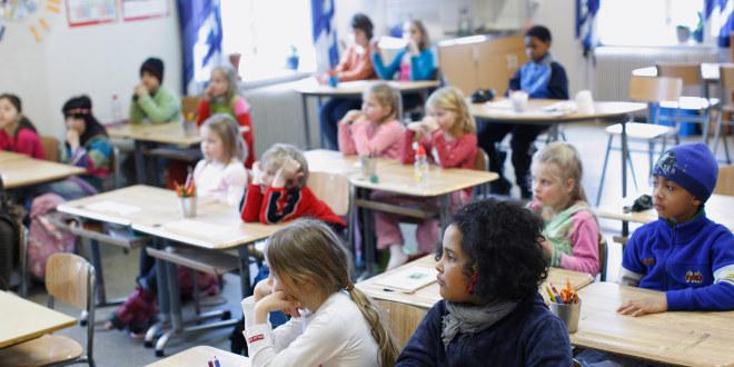 Fra et klasserom med to og to elever ved samme pult. Vi ser ikke læreren, alle elevene ser samme vei.