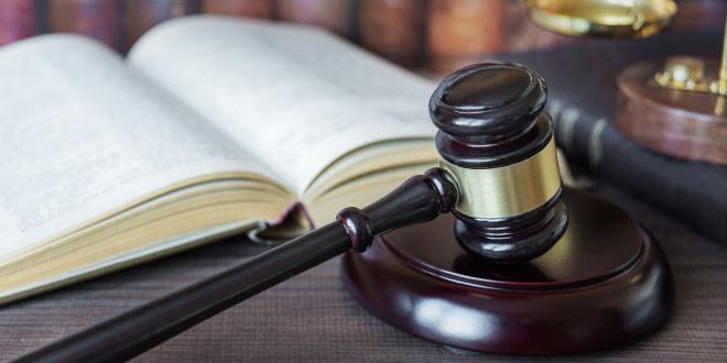 Åpen bok og hammer brukt av dommere i rettsal.
