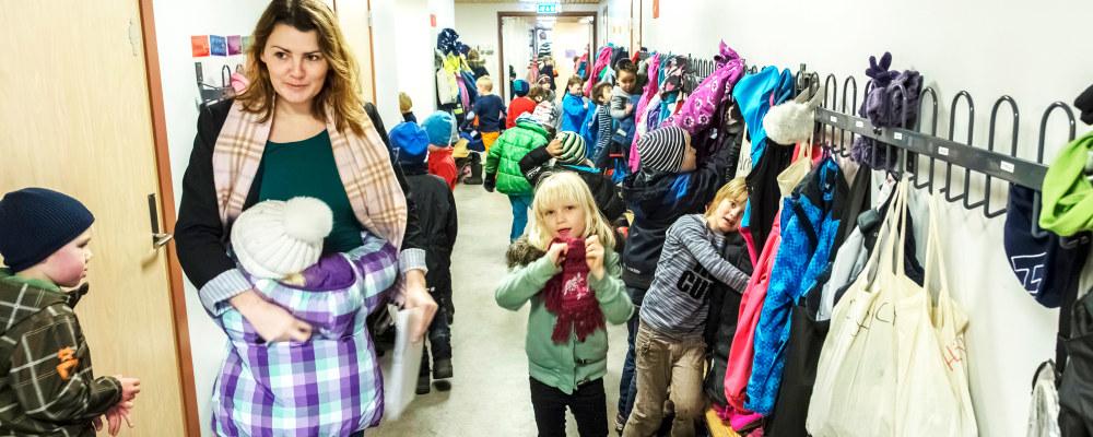 Lærer klemmer elev på barnetrinnet i korridoren, mens andre elever kler på seg yttertøyet.