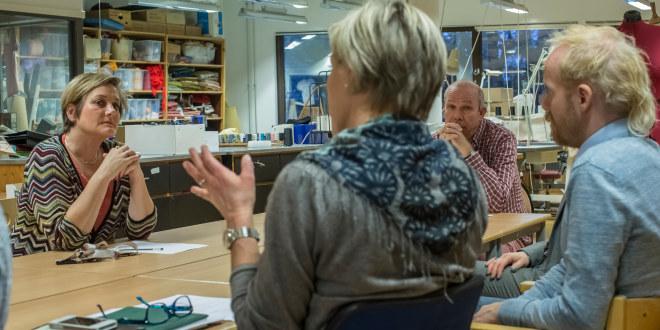 Lærere sitter rundt et bord og diskuterer