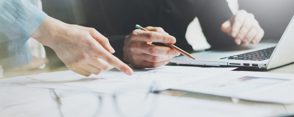 To personer holder på med papirarbeide. Nærbilde av hendene som peker på detaljer på et ark.