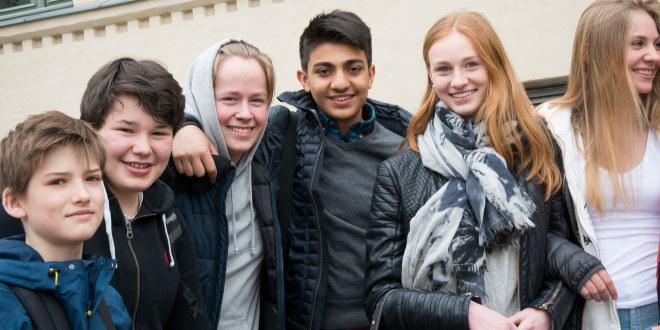 Seks blide skoleelever står tett sammen i skolegården. De smiler til fotografen.