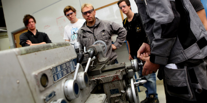 Lærer og tre elever som ser på at en fjerde elev skrur på en maskin