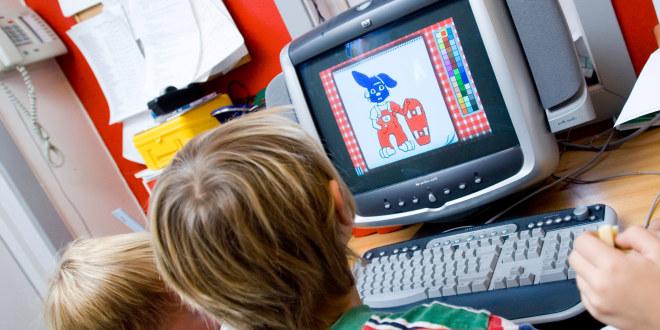 To barnehagebarn som ser på en PC