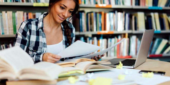 Ung, kvinnelig studenter leser på biblioteket. Omkranset av mange bøker og papirer.
