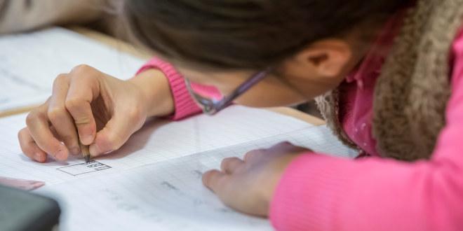En jente som skriver i en bok