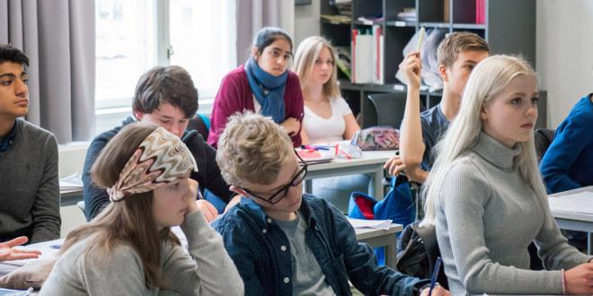 Elever i klasserom ved pultene. Lytter til læreren. Noen skriver.