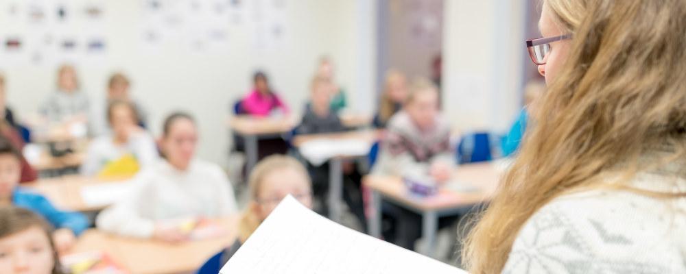 Lærer står foran stor klasse i klasserom.