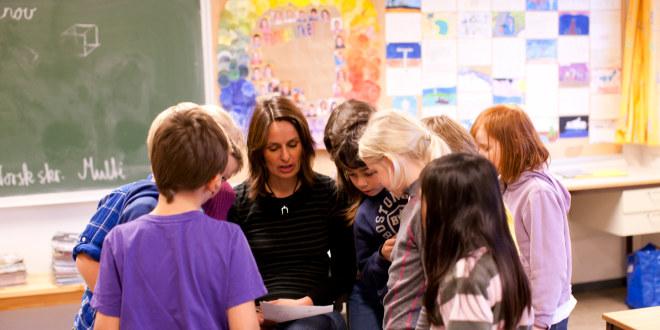 Elever i barneskolealder samlet rundt læreren som leser fra et ark, i klasserommet.