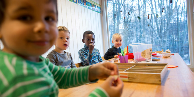 A group of four boys around a table in a kindergarten. All of them looking at the photographer