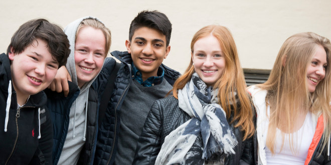 A group of five smiling teenagers in a school yard, looking at the photographer.