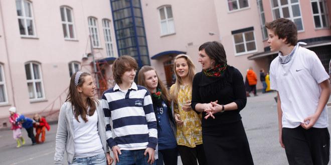 Lærer prater med en gruppe elever i ungdomsskolealder i skolegård.