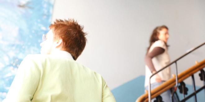 To lærere går opp en trapp med ryggen til.