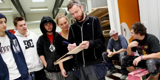 Lærer står og viser stående elever noe med en penn på en blokk