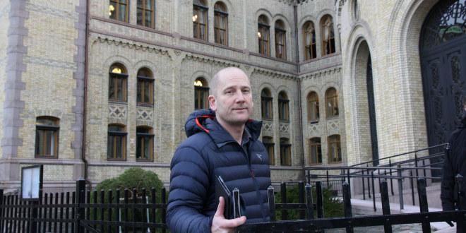 Steffen Handal står ved porten til Stortinget.