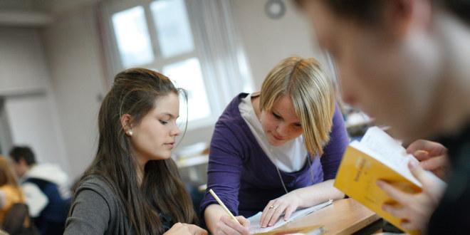 Fra et klasserom. En lærer hjelper en av elevene og noterer noe.