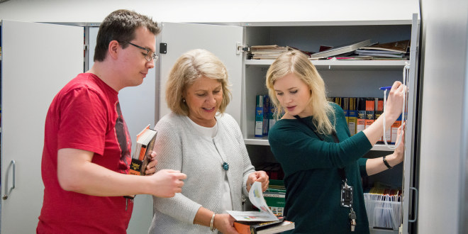 Tre lærere samtaler om innholdet i en brosjyre den ene av dem har.