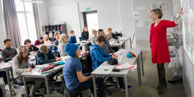 En dame som peker på en tavle foran en gruppe elever.