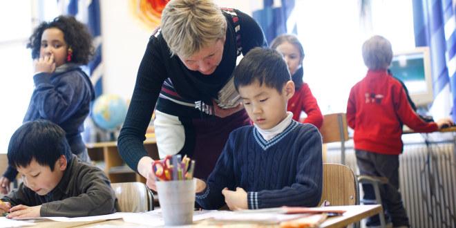 Lærer i klasserom står bøyd over elev og hjelper eleven med oppgaven