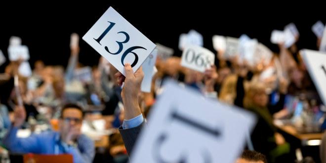 Delegater viser stemmetegn på landsmøtet. Lapp med nr 136.