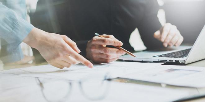 To personer sitter foran pc og samarbeider med tekst på et ark. Nærbilde av hendene deres.
