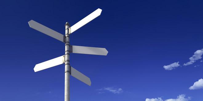 Veiskilt i ulike retninger mot blå himmel.