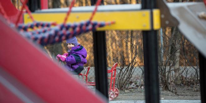 Ett barn i lille dress på sykkel i en barnehage.