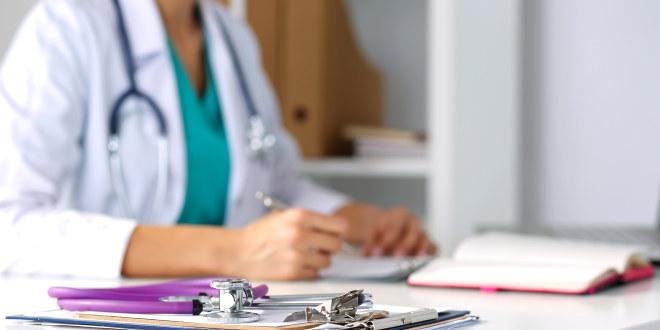 Bilde fra legekontor med lege som skriver.