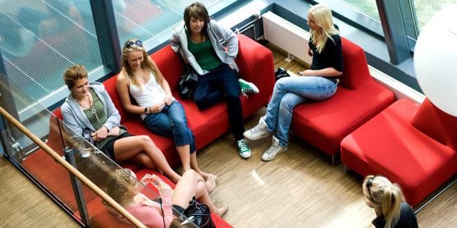 Elever på videregående sitter og prater sammen på skolen.