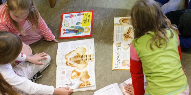Tre jenter sitter på gulvet og leser bøker om kroppen.
