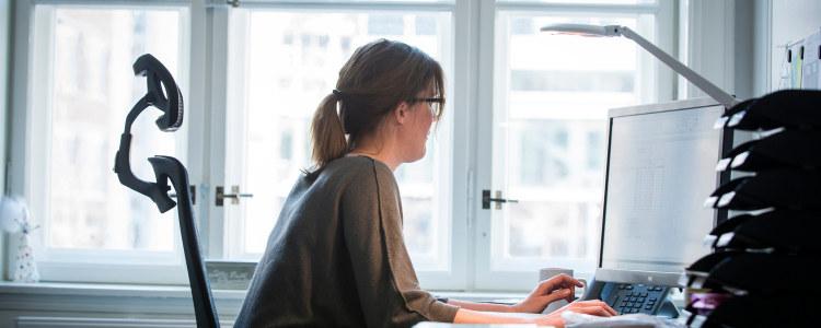 Kvinne foran PC-skjerm.