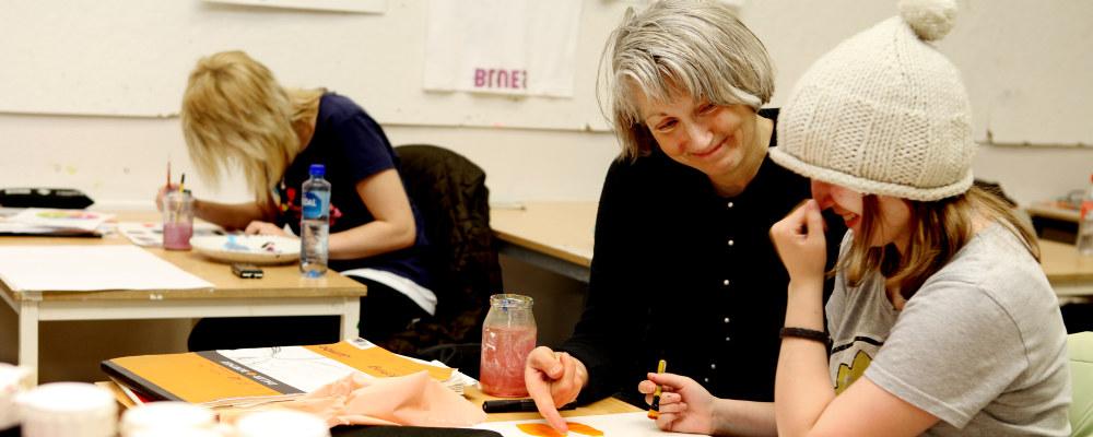 Smilende kvinnelig lærer i et klasserom peker på maleriet på pulten til en av elevene. Eleven fniser.