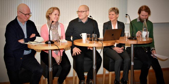 Paneldebatt med flere deltagere som smiler.