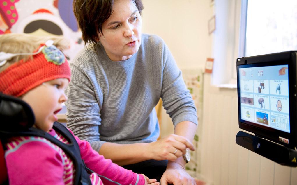 Mia kommuniserer gjennom symboler, her på en dataskjerm. Hun fester blikket på symbolet hun vil uttrykke til spesialpedagog Jaana Salamonsen. Foto: Ingun A. Mæhlum
