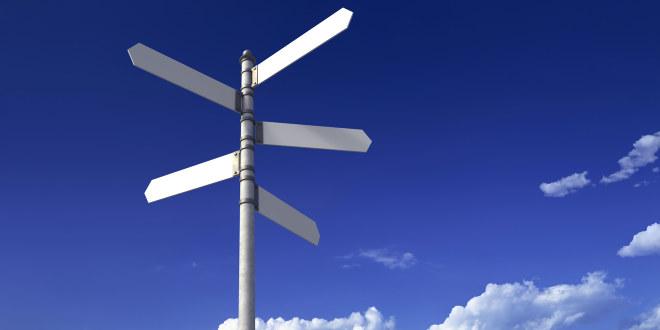 Et veiskilt med pekere i flere retninger. Det står ikke noe på de enkelte skiltene. I bakgrunnen en blå himmel med noen skyer