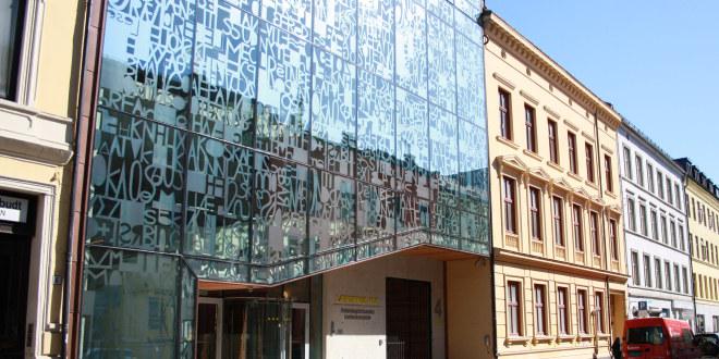 Bilde av glassvegg med masse bokstaver.