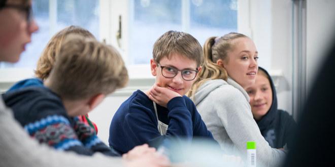 En gruppe elever sitter sammen ved et bord i en klasse. De ser blide og fornøyde ut.