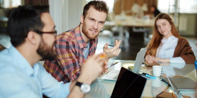 Unge voksne sitter rundt et bord med oppslåtte PCer og diskuterer.